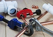 An plumbing themed set with wrench, spanner, cutter, copper pipes, joints and plumber service drawings